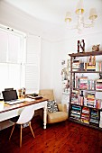 Bauhaus chair and desk below window next to armchair and antique bookcase in corner
