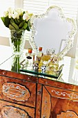 Perfume bottles on tray and romantic mirror with decorative frame on antique dressing table