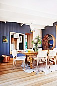 Dining area with animal-skin rug, rustic table and woven chairs in front of blue-painted wooden wall