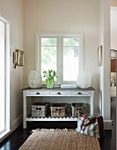Large lanterns and flowers on console table with drawers and storage baskets below window