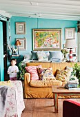 Sofa and double bed in interior with walls painted turquoise and gallery of pictures in background