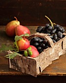 Basket covered in birch bark and filled with pears and grapes