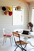 Various chairs in front of round table below arc lamp; colourful hats on Bauhaus coat rack on wall