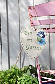 Hand-crafted, heart-shaped sign made from ecru felt with embroidered message and appliqué fabric roses hanging on rusty garden chair
