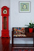 Telephone bench with patterned upholstery, framed picture and red-painted, antique longcase clock in wallpapered hallway