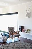 Pouffe and retro wooden armchair next to speaker and books on shelves; hunting trophy sculpture on wall
