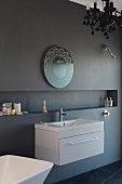 Ornate mirror and modern washstand on anthracite wall with long, narrow niche