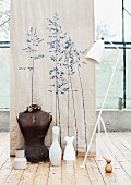 Wall decal of grasses on old linen fabric behind vintage standard lamp, tailors' dummy and vases