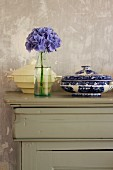 Hydrangea flower in bottle and two soup tureens on vintage sideboard