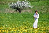 Woman making dandelion wreath in the field