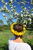 Woman wearing head wreath of dandelions in front of blossoming apple tree