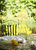 A break for refreshments, outdoors - lemons and lemon slices in front of a jug on water on a tiled table