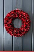 Door wreath of red pinecones and curled wood shavings