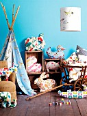Bright, patterned fabrics in child's bedroom made into stylised animal-shaped cushions, lampshade and indoor teepee