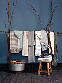 Scarves and blankets in pale, natural colours draped over frame made from long branches and stacked in zinc tub and on stool against blue wall
