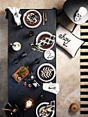 Blick von oben auf Gedecke mit karierten Stoffservietten auf grauer Tischdecke neben Hocker mit Totenschädel