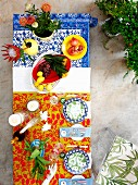 Colourful table atmosphere - view down onto colourful place settings and vases of tropical flowers