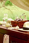 Bottles of perfume and sunglasses on hat on antique chest of drawers