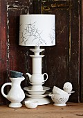 Table lamp with original base made from stacked china crockery against wooden back boards with peeling paint