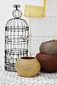 Old, ornate bird cage and various round baskets with wire rack in background