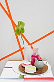 Containers on plate in front of geometric pattern of orange paper strips on wall
