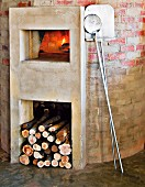 Masonry pizza oven with plastered log pile and oven surround; pizza peels leaning on wall to one side