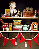 Stacked books, trophies and china bust of woman on simple shelves decorated with red bunting