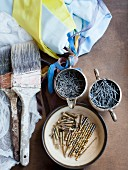 Still-life of paintbrushes, nails, screws & decorative fabrics
