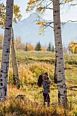 Woman carrying child in autumnal clearing