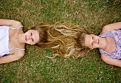 Two teenagers lying in meadow (top view)