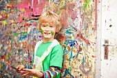 Boy with paintbrush against wall spattered with paint