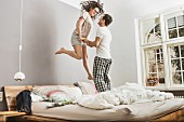 Couple in pyjamas bouncing on bed