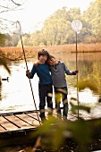 Two boys with dip nets standing on lake jetty