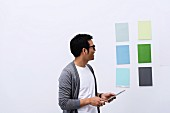 Man standing in front of various colour cards on wall