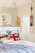 Union Flag scatter cushions on double bed and ensuite bathroom behind half-height wall with maritime decor