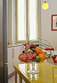 Arrangement of fruit in glass pedestal fruit bowl on yellow painted table with white base units and tall window in background