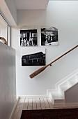 Treppenhaus mit Vintage Holz Handlauf und schwarz-weisse Fotos an Wand