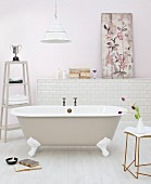 Free-standing, nostalgic bathtub and side table; picture leaning against wall on masonry shelf in background
