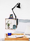 White wooden crate mounted on wall and painted white inside with ornaments and clip lamp used as bedside cabinet; breakfast tray made from crate in blurry foreground