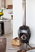 Ceramic stove filled with wood on stainless steel panel in open-plan interior