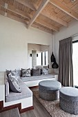 Masonry corner bench with scatter cushions on grey seat cushions and pair of grey ottomans