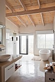 White, modern bathroom with wooden ceiling and free-standing bathtub below window next to rainfall shower and glass sliding door leading outdoors