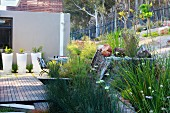 White planters on wooden deck outside contemporary house in landscaped gardens