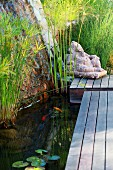 Stone figure at end of wooden jetty next to pond with aquatic plants
