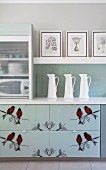 Silhouettes of birds on drawers of kitchen base unit; white china jugs on counter and framed drawings on shelf