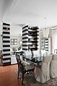 Dining table with glossy, black top and loose-covered chairs; partition shelving in wide black and white stripes in background