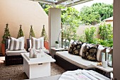 Seating area on roofed terrace; dark rattan furniture with pale seat cushions and scatter cushions in floral patterns and broad stripes