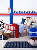 Vintage bed with red metal frame and candlesticks on blue metal box on castors in front of wave motif painted on wall