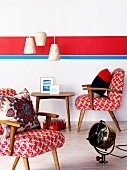 Fifties-style armchairs and side table and vintage floor lamp in front of wall with brightly coloured stripes