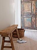 Trainers below rustic bench and rattan basket on wooden floor; weathered door in background